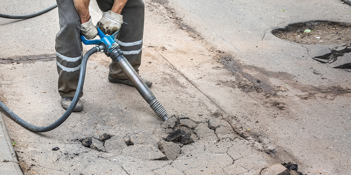 A public works technician is fixing faulty road infrastructure