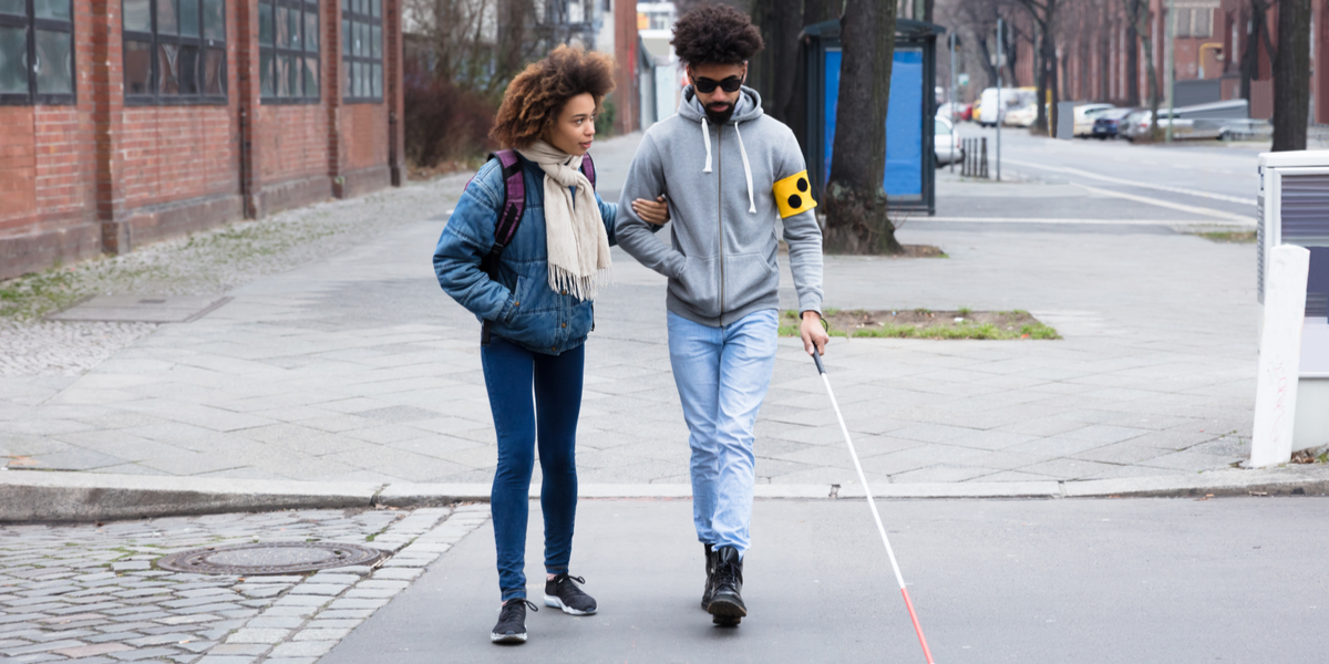 A video of a woman helping a blind man cross the street.