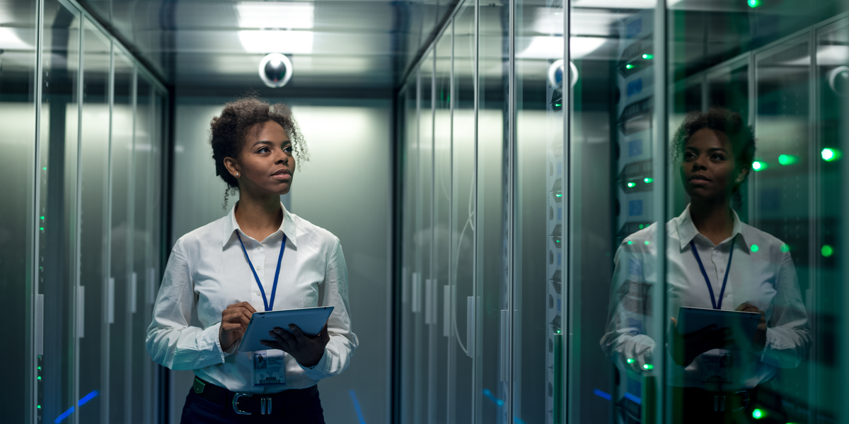 A woman walking in a datacenter with encrypted drives